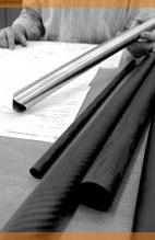 filament wound carbon fiber and titanium tubes on a desk