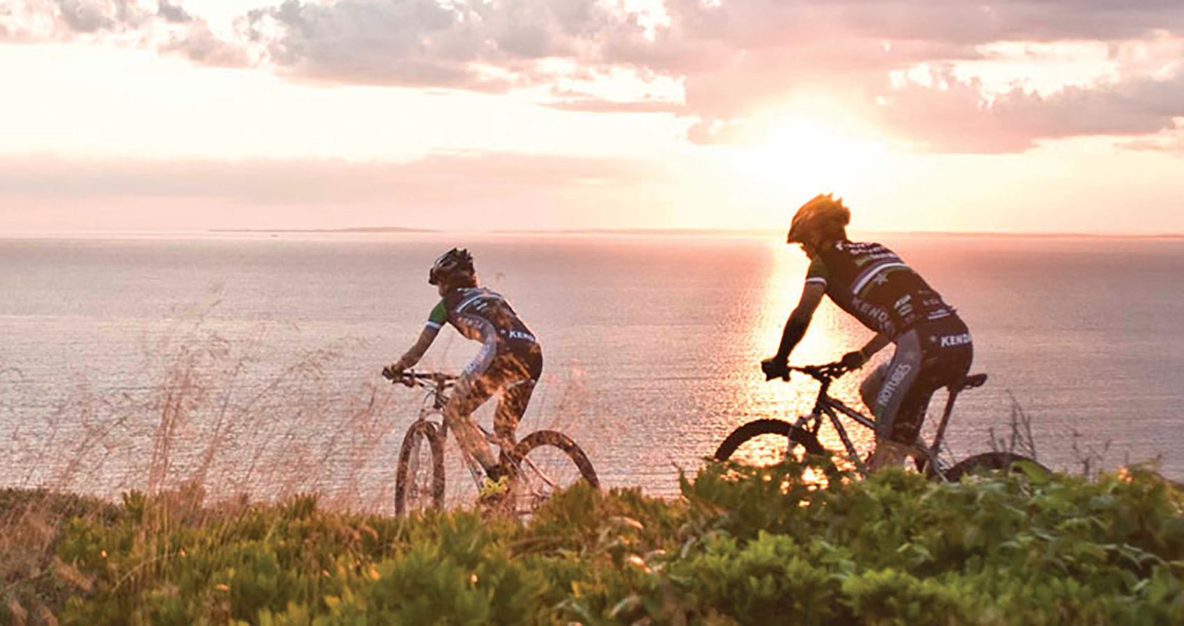Mike Broderick and Mary McConnenoug ride their Solas into the Sunrise near the ocean
