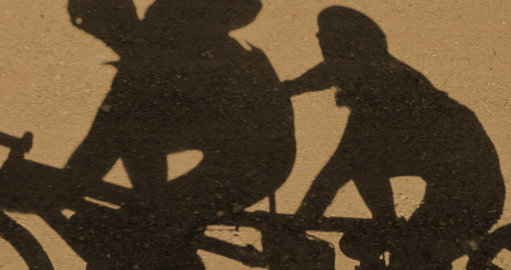 the shadow of a couple riding their mountain tandem bike dances on the dirt