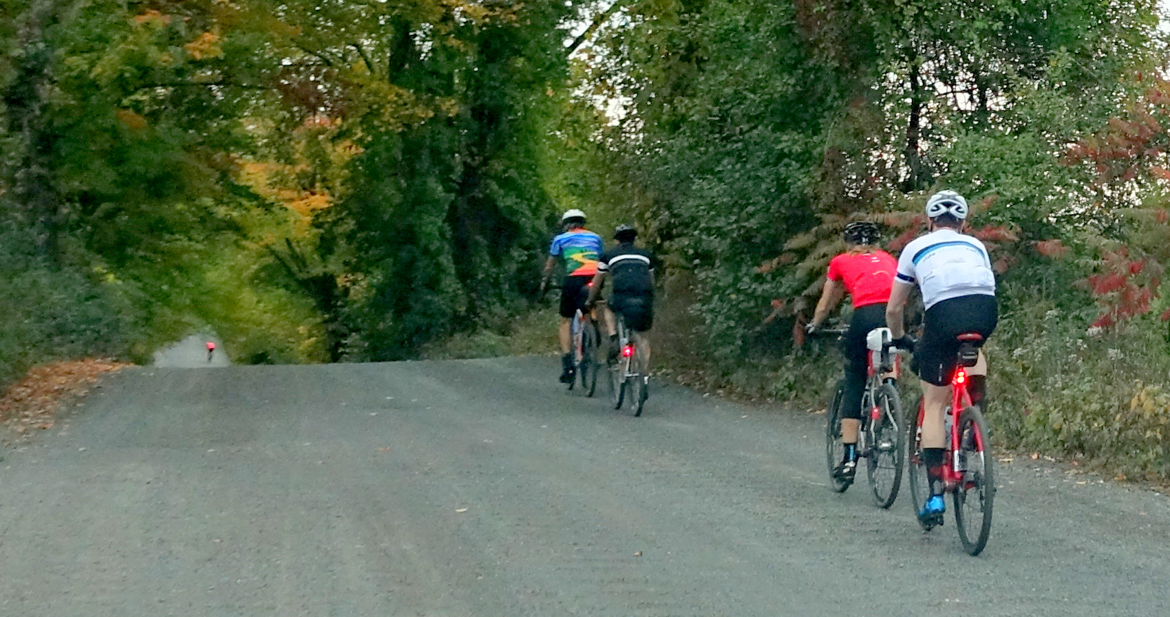 four cyclists on a rolling gravel road