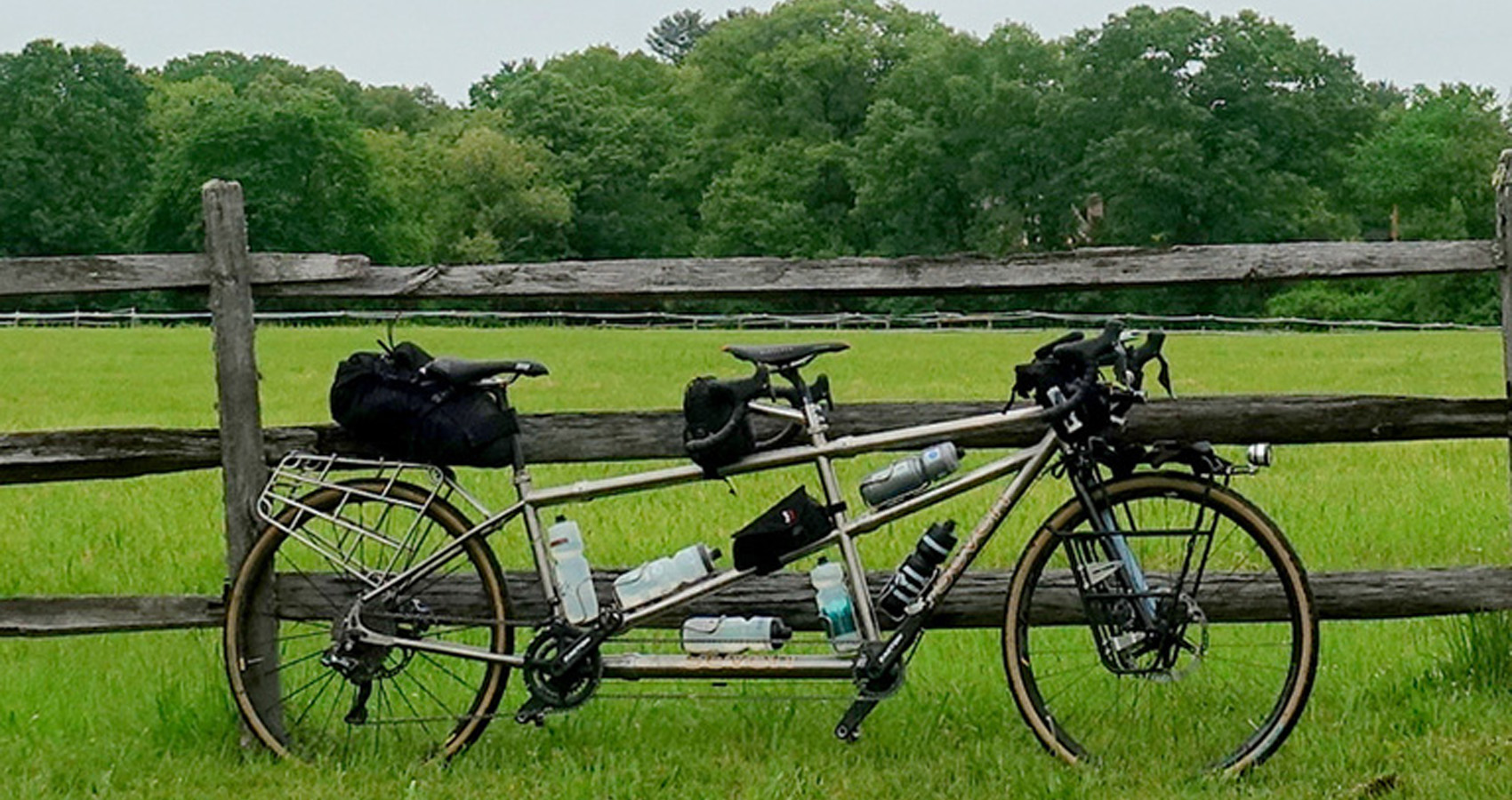 a titanium tandem bicycle loaded for a day-long tour rests against a rustic farm fence