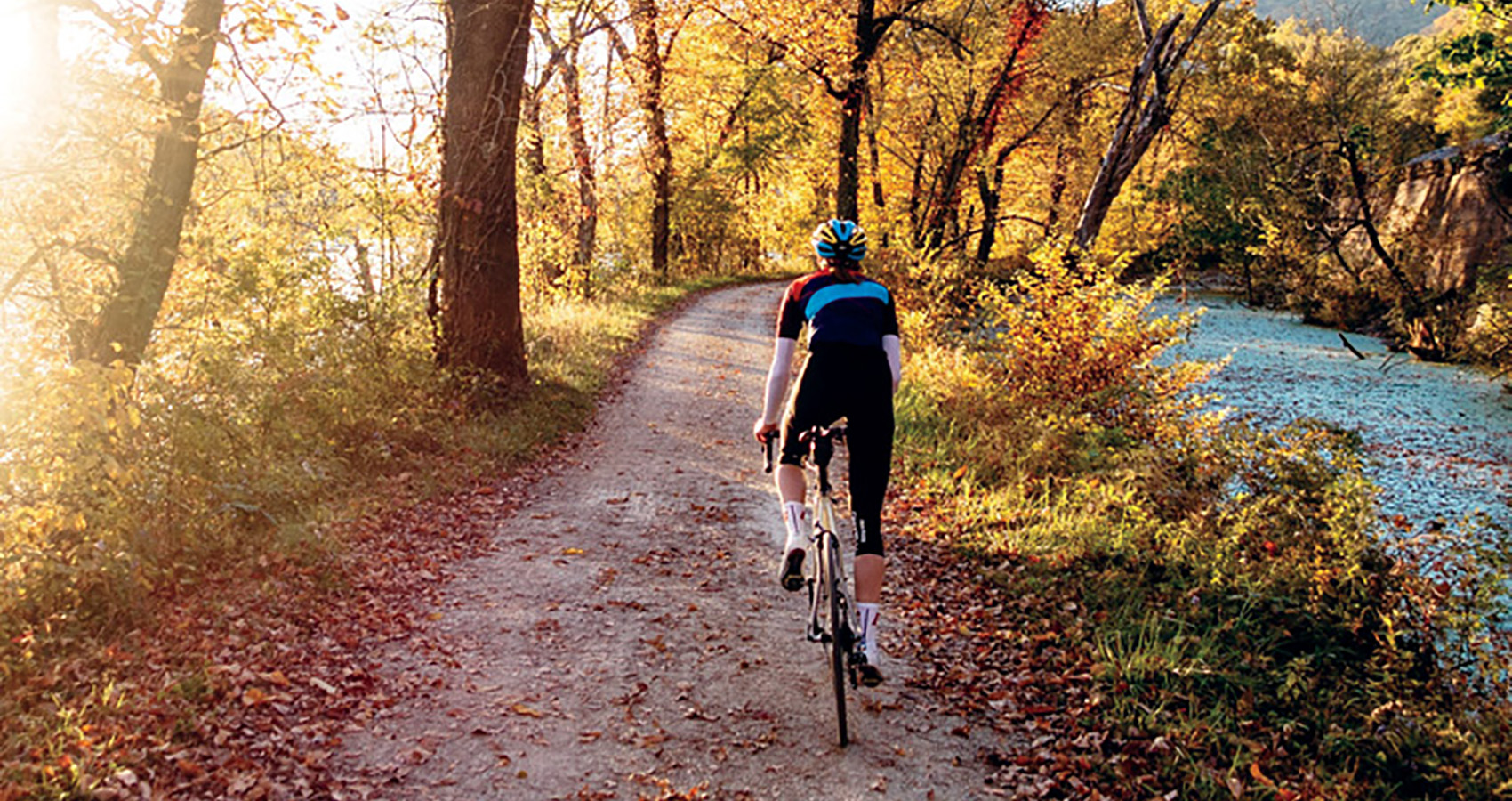 solo rider on a leaf-speckled path by a srteam on a New England autumn morning