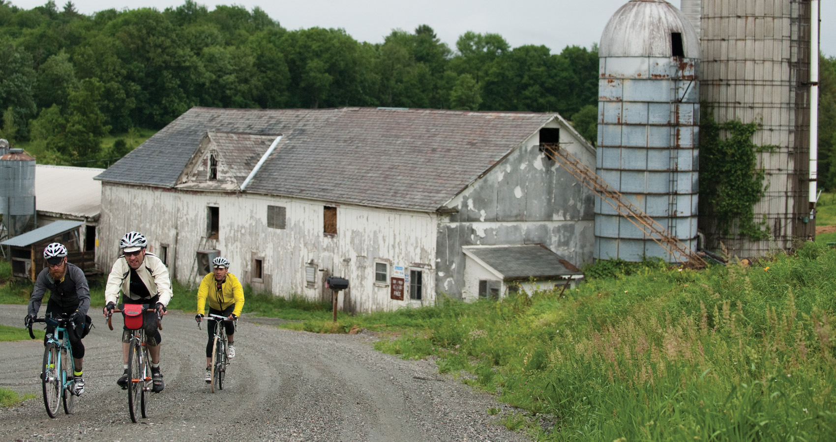 three riders pass a quaint farm in Vermont on a gravel road